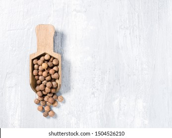 Allspice (Jamaica pepper) on a wooden scoop on a gray background vertically