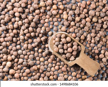 Allspice (Jamaica pepper) in a wooden scoop on allspice background diagonally