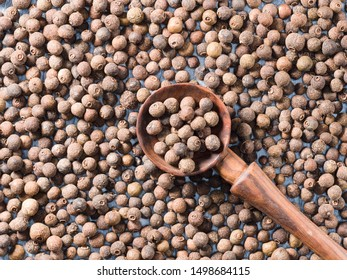 Allspice (Jamaica pepper) in a wooden spoon on allspice background diagonally
