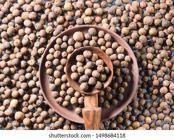 Allspice (Jamaica pepper) in a wooden spoon and clay plate on allspice background