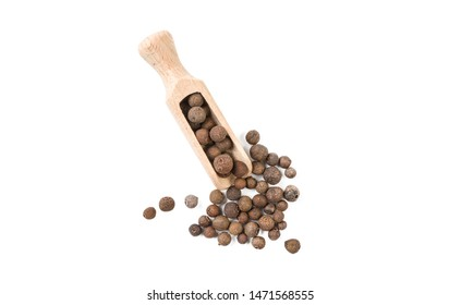 allspice jamaican pepper in wooden scoop isolated on white background. top view. spices and food ingredients.