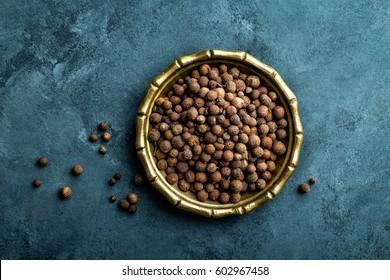 Allspice pepper, peppercorns on dark culinary background, top view, copy space