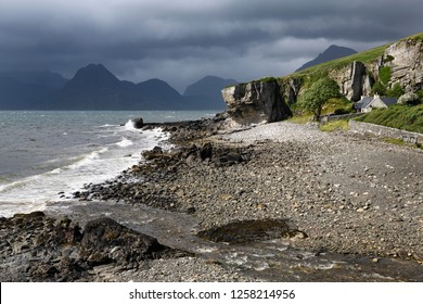 Allt Port na Cullaidh river at Elgol beach with Red Cuillin Mountains under clouds at Loch Scavaig Scottish Highlands Isle of Skye Scotland