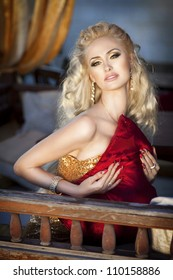 alluring blond relaxing in luxury interior. Stylish rich slim girl in sexy golden dress with healthy glossy curly hair at hotel villa apartment. Fashion glamorous shot at vacation resort spring-summer