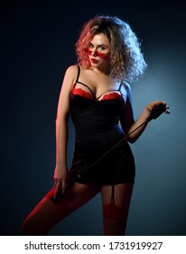 Alluring, blonde curly girl in sunglasses, red and black lace sexy lingerie chemise, stockings stands holding whip over dark background. Beauty, fashion, advertising