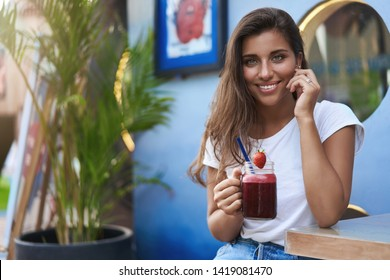 Alluring cute flirty young girl tanned brunette, touch cheek joyfully smiling hold strawberry shake smoothie listen interesting story look coquettish have romantic date outdoor cafe street terrace