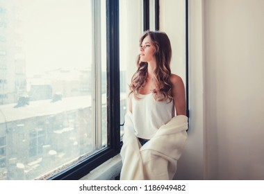 Alluring girl in white plaid posing on a apartment by the window. Beautiful girl in a cozy room.