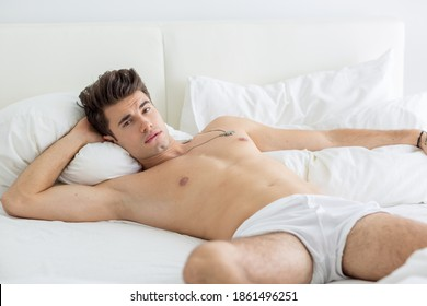 Alluring sexy male model lying in bed shirtless wearing underwear and seducing the camera by biting lips.