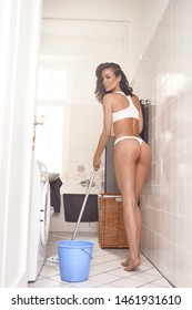 Alluring sexy slender middle-aged brunette woman in white underwear with mop and bucket posing in the scullery against a wall looking provocatively at the camera