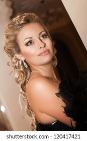 alluring sexy woman In evening dress in luxury interior. Stylish rich slim girl with hairstyle and bright makeup in apartment. beautiful fashion blond in fur and diamond jewelery smiling in hotel hall