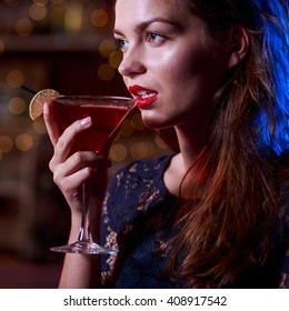 Alluring woman in black dress drinking cocktail