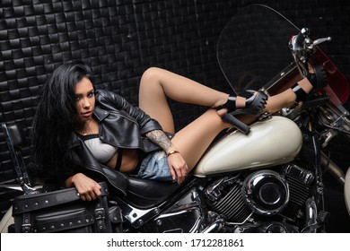 Alluring woman dressed in a leather jacket and shorts lying on a motorcycle