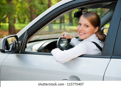 alluring young woman driving the car and smiling