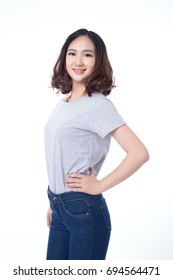 alluring young woman in white t-shirt and blue jeans posing over white background