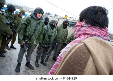 AL-MASARA, PALESTINIAN TERRITORIES - FEBRUARY 10: Palestinian activists confront Israeli soldiers to protest the separation wall on a rainy Friday in the West Bank village of Al-Masara on Feb 10, 2012
