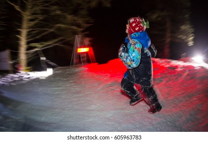 ALMATY, KAZAKHSTAN - 18 FEBRUARY 2017: Night competitions in the foothills of the city of Almaty, in the Trailrunning and Skyship discipline, which is called TunRun winter edition. Happy girl running