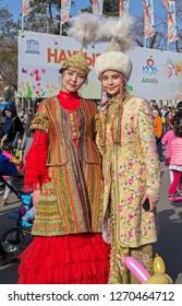 Almaty, Kazakhstan - 22 March 2016: Two young women in national Kazakh costumes at celebration of Nauryz. Words: 'Nauryz'