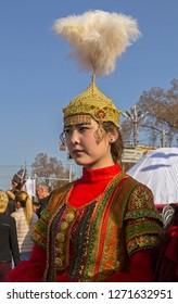 Almaty, Kazakhstan - 22 March 2016: Young woman in national Kazakh costume at celebration of Nauryz. Words: 'Panvilov. Furmanov' - names of streets