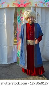 Almaty, Kazakhstan - 22 March 2016: Man in colorful costume of medieval Persian merchant at celebration of Nauryz. Red hair & beard.