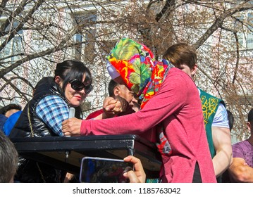 Almaty, Kazakhstan - 22 March 2018: Two Asian women (modern biker & traditional islamic girl) struggling at street arm restling tournament during Nauryz celebration.