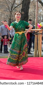 Almaty, Kazakhstan - 22 March 2018: Young woman performing Indian dance in street at celebration of Nauryz