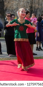 Almaty, Kazakhstan - 22 March 2018: Young girl performing Indian dance in street at celebration of Nauryz. Selective focus