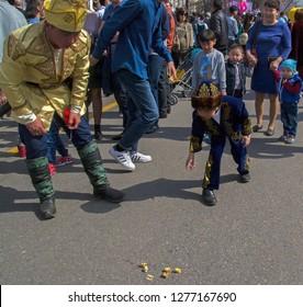 Almaty, Kazakhstan - 22 March 2018: Boys in national Kazakh costumes playing 'asyk' (ancient nomad bowling) at celebration of Nauryz