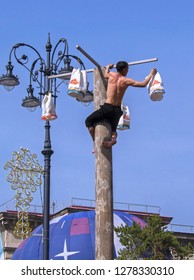 Almaty, Kazakhstan - 22 March 2018: Winner of competition on climbing taking prize from wooden pole at Nauryz. Traditional folk sport & entertainment