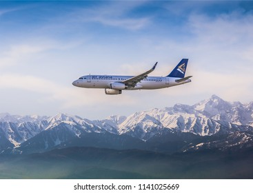 Almaty, Kazakhstan. 28 June 2018. Passenger airplane AIRBUS A320 Air Astana Airlines is flying on the mountain background.