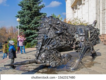 Almaty, Kazakhstan - 3 Nov 2018: Central Museum of Kazakhstan. People looking at metal sculpture of bull at entrance made of parts of old cars & mechanisms