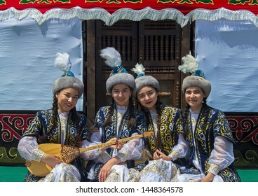 Almaty, Kazakhstan - 7 June 2019: Ethnic Festival 'Uly Dala' (Great Steppe). Girls in national Kazakh costumes near traditional yurt. Dombra.