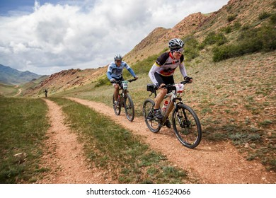 """ALMATY, KAZAKHSTAN - APRIL 30, 2016: Two unknown riders in action at Adventure mountain bike cross-country competition in mountains """"Jeyran Trophy 2016"""""""
