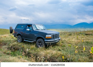 Almaty / Kazakhstan - Aug 2018: Ford Bronco in Tian Shan mountains near Almaty.  The green Ush Konir plato with juice meadows in good weather.