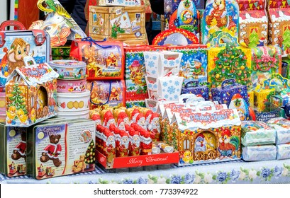 "Almaty, Kazakhstan - Dec 27, 2016: Boxes of chocolate as traditional Christmas gifts at street market with words ""Merry Christmas"" in three languages - English, Russian & Kazakh. Selective focus"