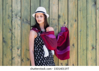 Almaty, Kazakhstan - July 08, 2019: Young beautiful babywearing mother carry her newborn baby in a ring sling on a rural green wooden wall background.