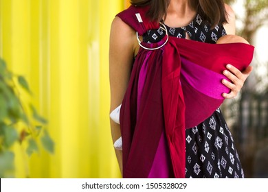 Almaty, Kazakhstan - July 08, 2019: Young beautiful babywearing mother carry her newborn baby in a ring sling in an urban scene.