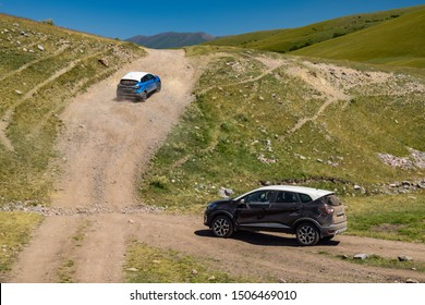 ALMATY, KAZAKHSTAN - JULY 20, 2019: French SUV Renault Koleos drives off road in Kazakstan. The SUV rides steep uphill on gravel and rocky path. Meadow  and hill landscape in the background.