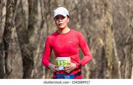 ALMATY, KAZAKHSTAN - March 16, 2019: a beautiful young unidentified girl runs through the woods during the spring marathon in the city of Almaty, in a grove named after Baum on March 16