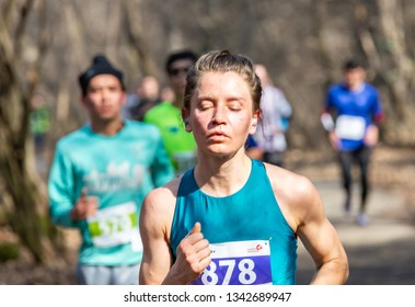ALMATY KAZAKHSTAN - MARCH 16 2019: a dense group of unidentified men and women runs through a grove during the spring marathon in the city of Almaty, in the grove named after Baum on March 16.