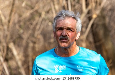 ALMATY, KAZAKHSTAN - March 16, 2019: portrait of an unknown old man who runs through the woods during the spring marathon in the city of Almaty, in the grove named after Baum on March 16