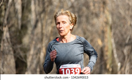 ALMATY, KAZAKHSTAN - March 16, 2019: portrait of a beautiful old woman who runs through the woods during the spring marathon in the city of Almaty, in a grove named after Baum on March 16