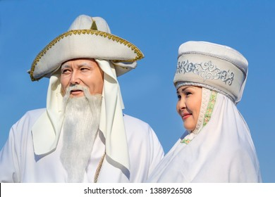 Almaty, Kazakhstan - March 21, 2019. Elderly men and women in white national Kazakh clothes against the background of the sky during the carnival holiday. Close-up. Portrait