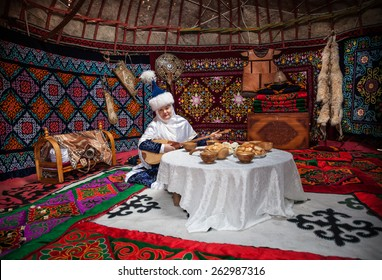 ALMATY, KAZAKHSTAN - MARCH 22, 2015: Woman in national Kazakh costume with dombra music instrument near the table with national food in Yurt nomadic house at Nauryz celebration