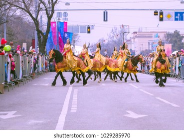Almaty, Kazakhstan - March 22, 2017: Young women riding horses in city streets representing ancient Scythians in golden costumes. Nauryz festival. Selective focus