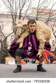 Almaty, Kazakhstan - March 22, 2017: Kazakh man lifting sheep (45kg) in street competition on Nauryz holiday. 'Koshkar koteru' - ancient traditional sport of nomads, weight lifting.