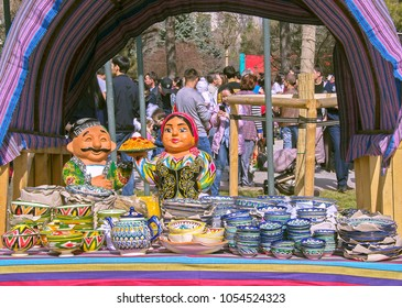 Almaty, Kazakhstan - March 22, 2018: Street-stand of handmade Uzbek pottery at Nauryz celebration. Ornamented bowls, cups, plates, dishes & biig ceramic figurines of Uzbek man & woman with pilaf.