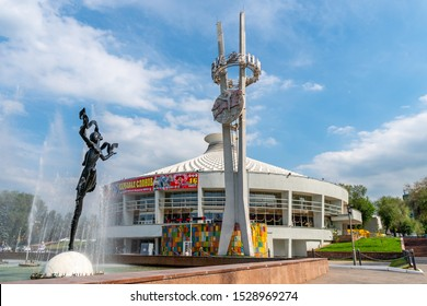 ALMATY, KAZAKHSTAN - MAY 2019: Kazakh State Circus Frontal View of a Stele and Dancing Woman Statue at a Fountain on a Sunny Blue Sky Day