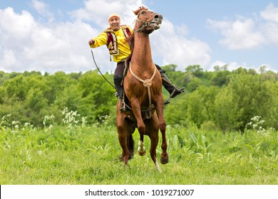 ALMATY, KAZAKHSTAN - MAY 31, 2017: Kazakh man in national costumes rides and tries to get his horse reared up, in Almaty, Kazakhstan.