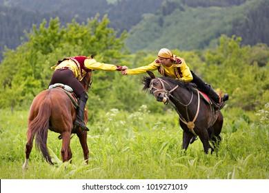ALMATY, KAZAKHSTAN - MAY 31, 2017: Kazakh men do traditional nomadic arm wrestling on their horse, in Kazakhstan.