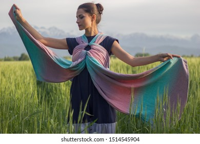 Almaty, Kazakhstan - May 31, 2018: Young beautiful babywearing mother carry her newborn baby in a ring sling in rural field scene.
